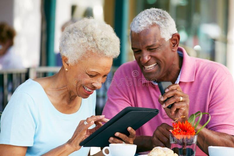 Pares mayores usando la tablilla en el café al aire libre foto de archivo