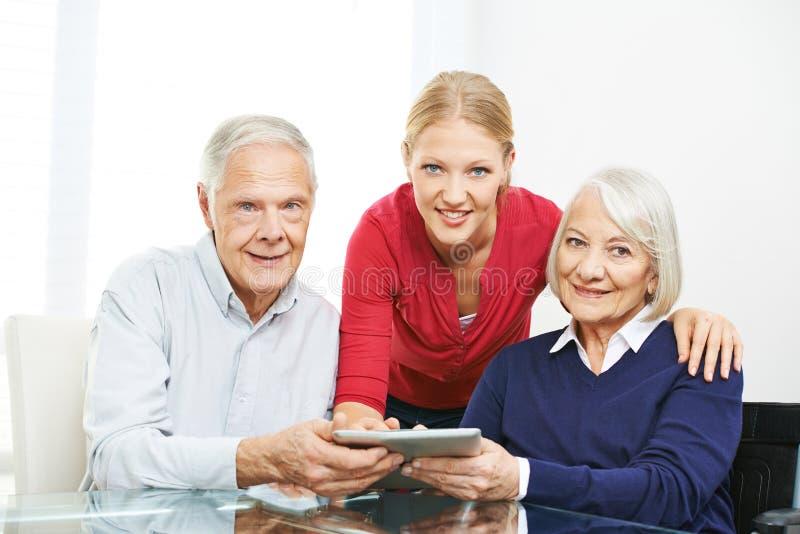 Pares mayores usando red social en la tableta fotografía de archivo libre de regalías