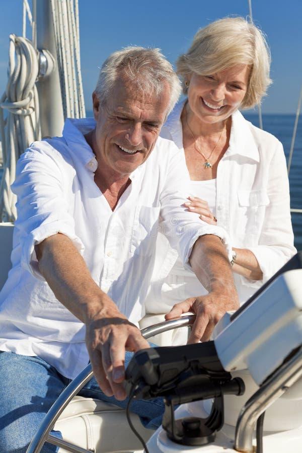 Pares mayores usando SatNav GPS en un barco de vela foto de archivo