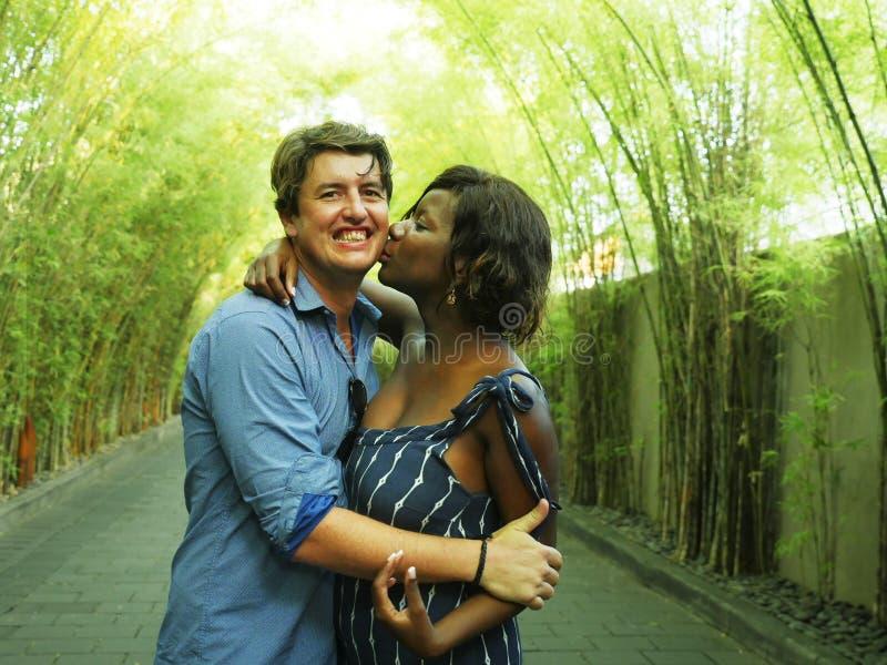Pares mezclados atractivos y felices de la pertenencia étnica que abrazan al aire libre con la novia o la esposa afroamericana ne fotos de archivo libres de regalías