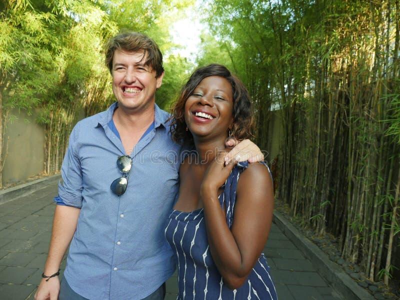Pares mezclados felices de la pertenencia étnica que abrazan al aire libre con la novia o esposa afroamericana negra atractiva y  fotos de archivo