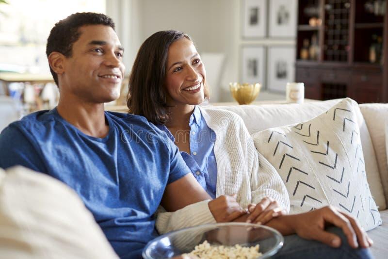 Pares milenares afro-americanos felizes que sentam-se no sofá em sua sala de visitas que olha a tevê e que come a pipoca, fim aci imagens de stock royalty free