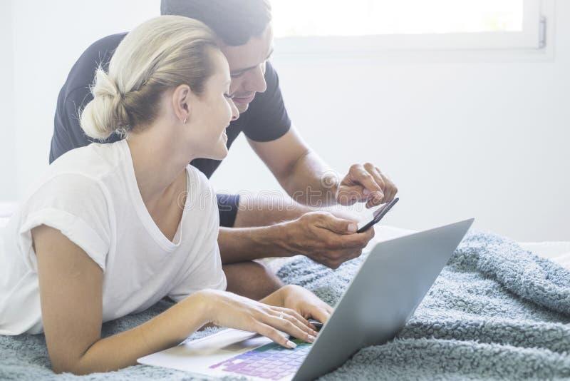Pares milenarios jovenes que trabajan en la cama en casa así como el amor y el concepto del equipo - forma de vida moderna de la  imágenes de archivo libres de regalías