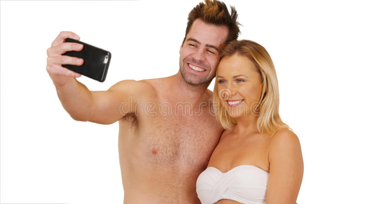 Pares milenarios que toman selfies en el fondo blanco fotos de archivo