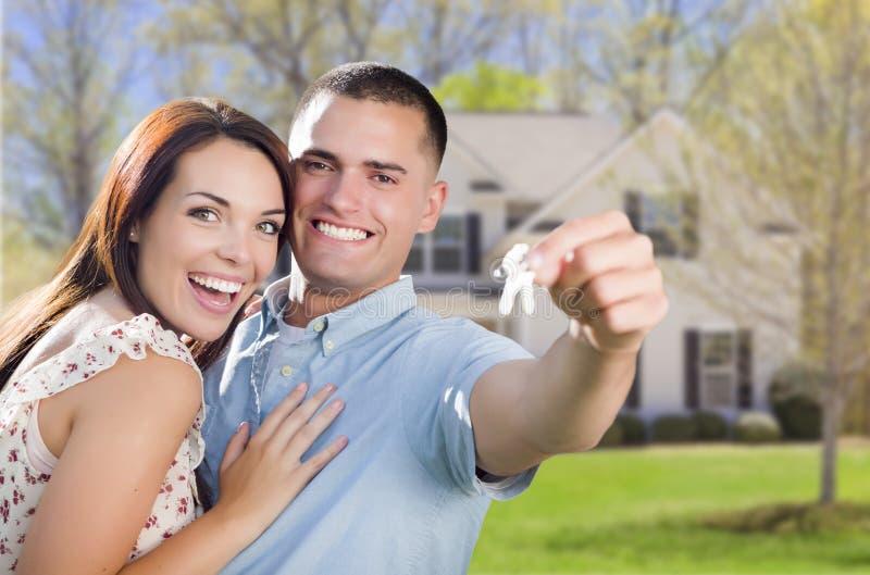 Pares militares com chaves da casa na frente da casa nova imagem de stock royalty free