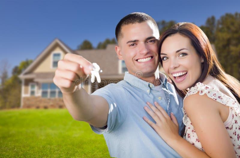 Pares militares con llaves de la casa delante del nuevo hogar imagenes de archivo