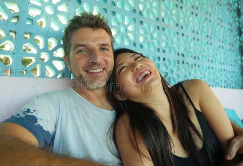Pares misturados bonitos e felizes novos da afiliação étnica no sorriso do amor alegre junto com o homem caucasiano considerá imagens de stock royalty free