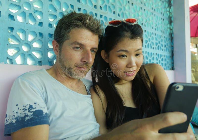 Pares misturados da afiliação étnica no sorriso do amor alegre com o homem caucasiano considerável e a mulher chinesa asiáti fotografia de stock