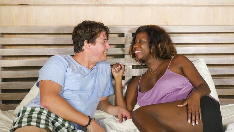 Pares misturados da afilia??o ?tnica no amor que afaga junto em casa na cama com a mulher americana do africano negro brincalh?o  imagem de stock