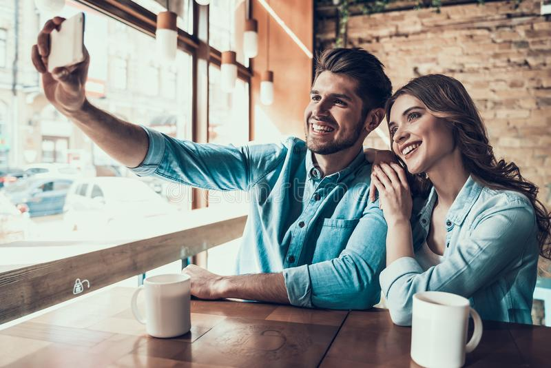 Pares modernos jovenes que toman las imágenes de ellos mismos en el teléfono, sentándose en la tabla en café imagenes de archivo
