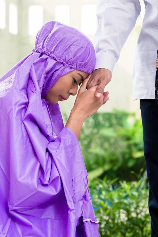 Pares muçulmanos asiáticos, homem e mulher, rezando em casa fotografia de stock royalty free