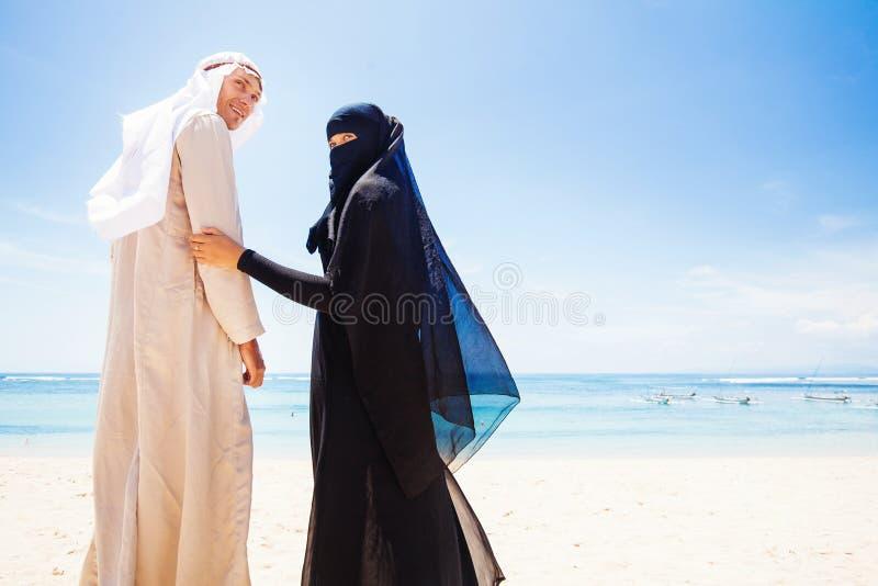 Pares muçulmanos em uma praia imagens de stock