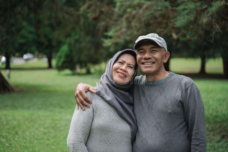 Pares muçulmanos no parque que sorri e que olha a câmera fotos de stock royalty free