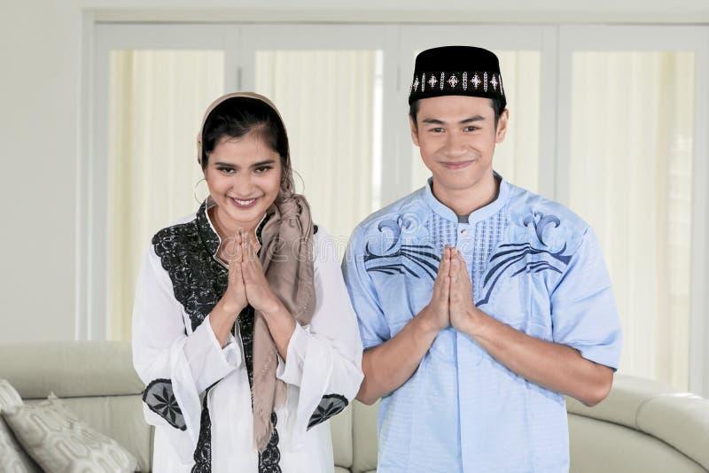 Pares muçulmanos que dão as mãos de cumprimento em casa foto de stock royalty free
