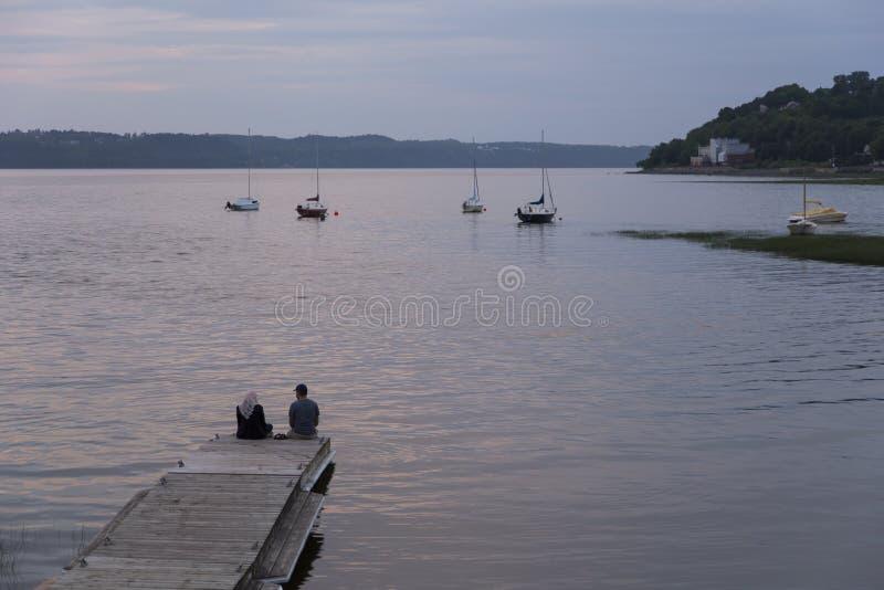 Pares muçulmanos que sentam-se em um molhe de madeira que aprecia uma noite azul da hora do verão na costa do St Lawrence River imagem de stock