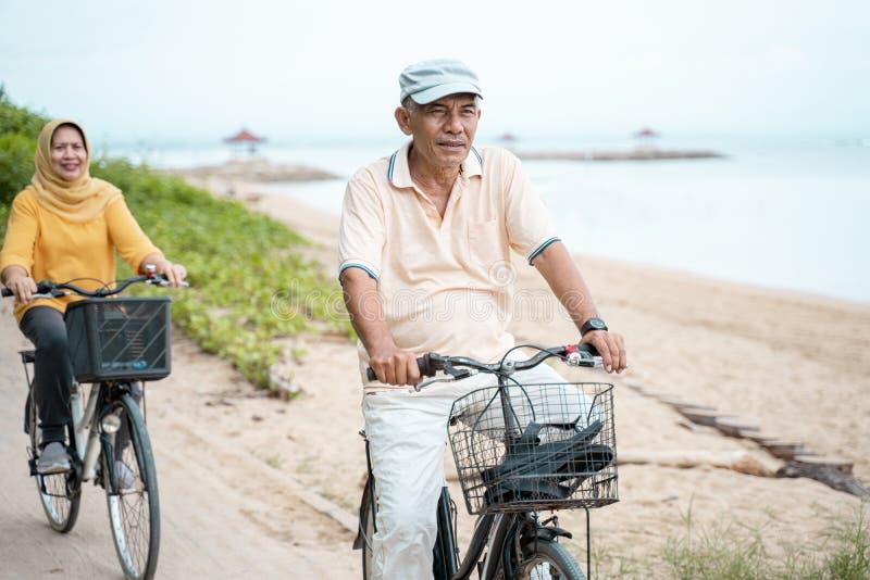 Pares muçulmanos superiores felizes que exercitam a bicicleta de montada junto fotografia de stock royalty free