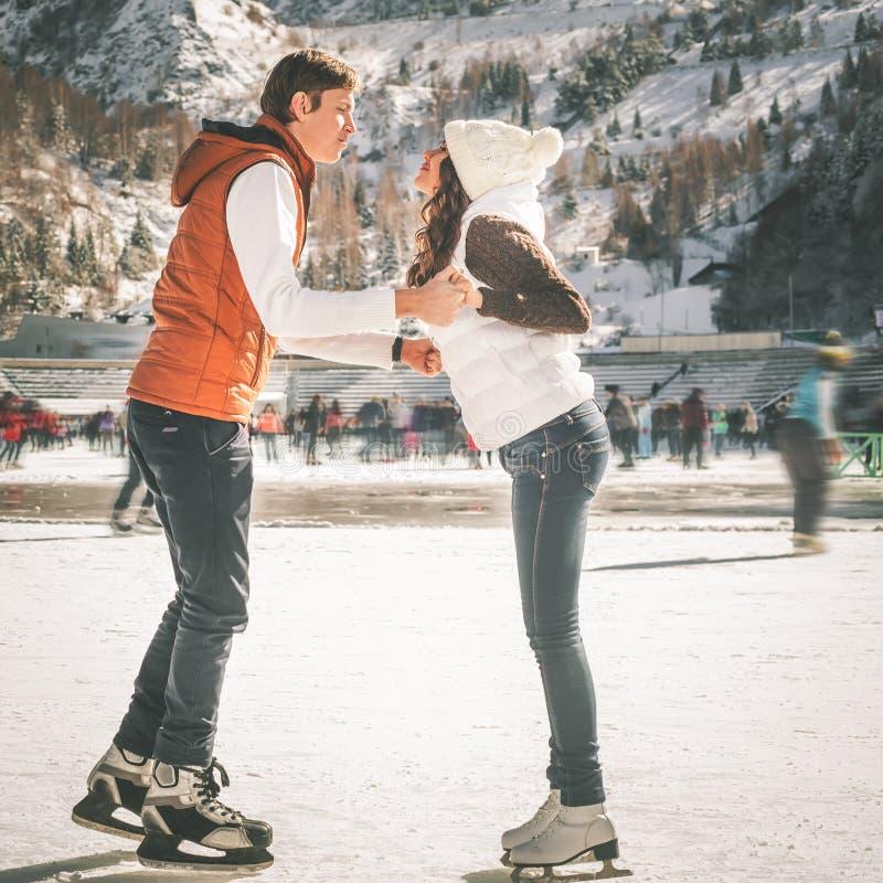 Pares, muchachas felices y patinaje de hielo del muchacho al aire libre en la pista fotografía de archivo libre de regalías