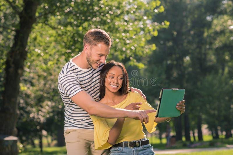 Pares multiétnicos alegres que toman el selfie en la tableta digital en parque fotografía de archivo libre de regalías