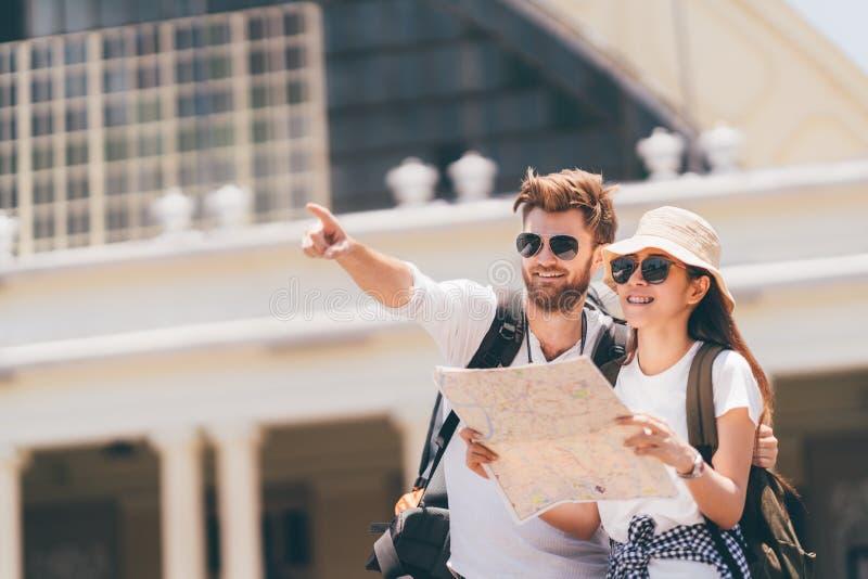 Pares multiétnicos del viajero usando mapa local genérico junto el día soleado Viaje de la luna de miel, turista del backpacker,  foto de archivo