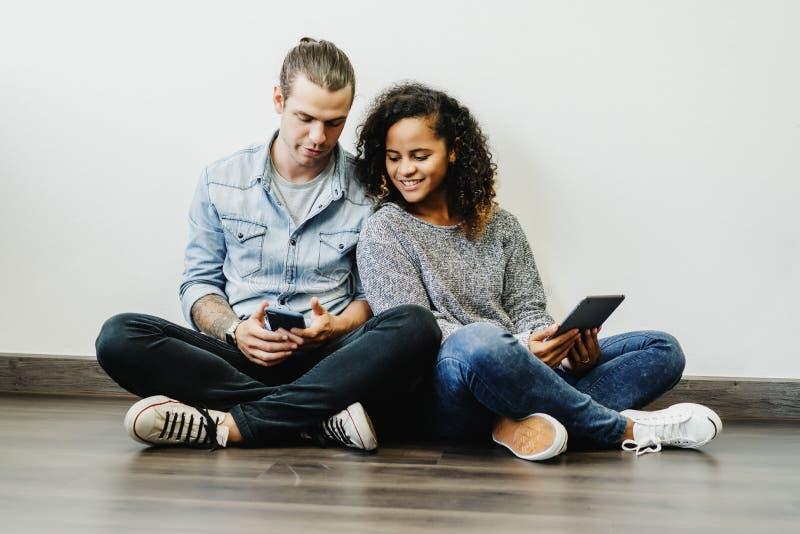 Pares multi-étnicos novos de sorriso usando a tabuleta digital junto em casa Povos, uma comunicação e conceito datar imagem de stock royalty free