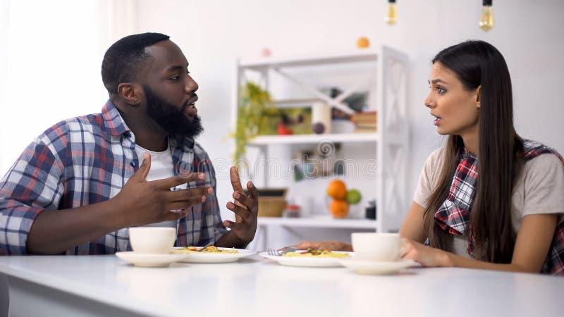 Pares multi-étnicos preocupados que discutem durante o almoço em casa, problemas do relacionamento imagem de stock royalty free