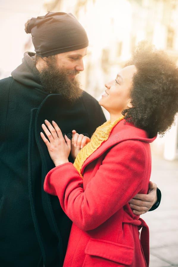 Pares multi-étnicos românticos no amor que abraça na rua fotografia de stock