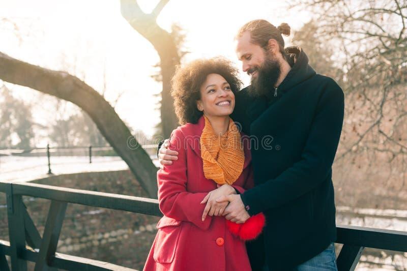 Pares multi-étnicos românticos no amor que abraça na rua foto de stock