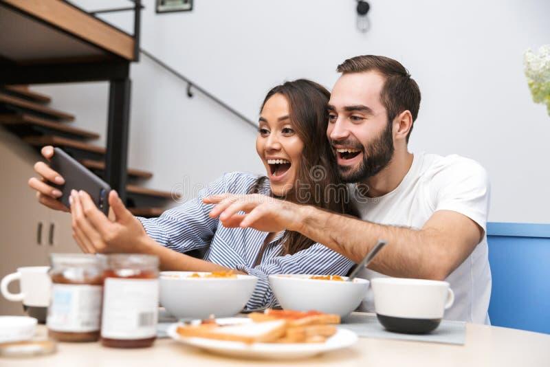 Pares multi-?tnicos felizes que comem o caf? da manh? imagens de stock