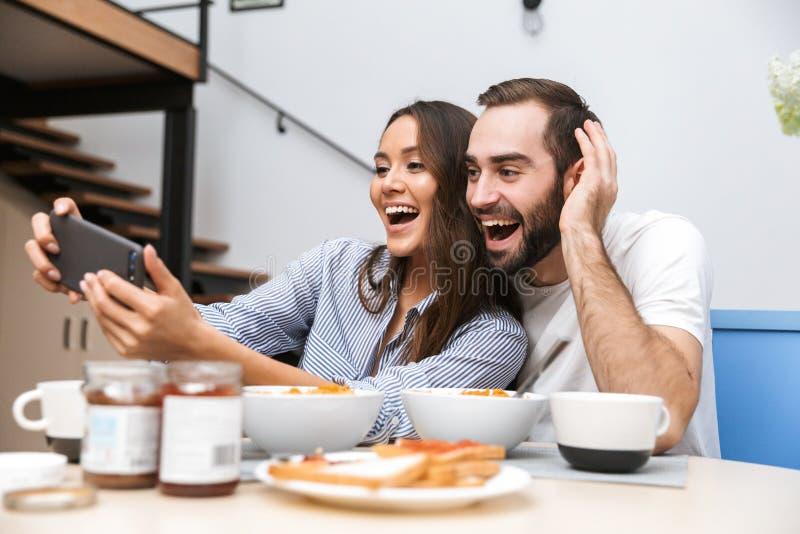 Pares multi-?tnicos felizes que comem o caf? da manh? imagem de stock royalty free