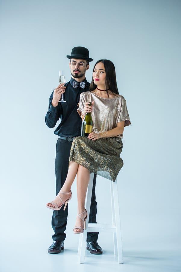 pares multiculturais elegantes com champanhe imagem de stock