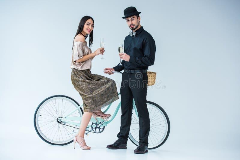 pares multiculturais elegantes com vidros do champanhe e da bicicleta fotografia de stock