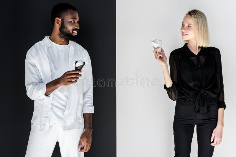 pares multiculturais que olham se com yin dos cones de gelado fotos de stock