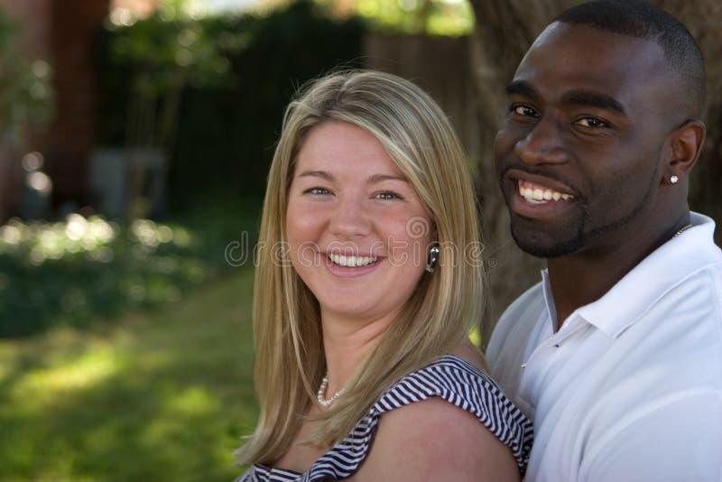 Pares multiculturales cariñosos felices que abrazan y que sonríen imagen de archivo