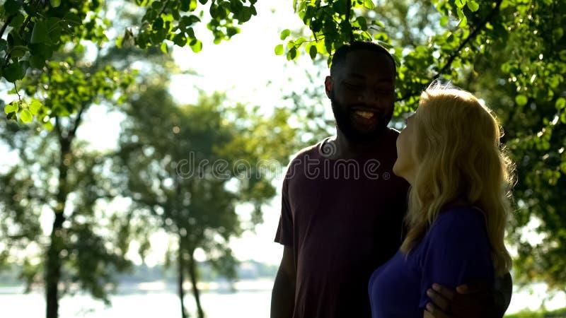 Pares multirraciais alegres que abraçam e que olham se no parque, estatística fotografia de stock royalty free