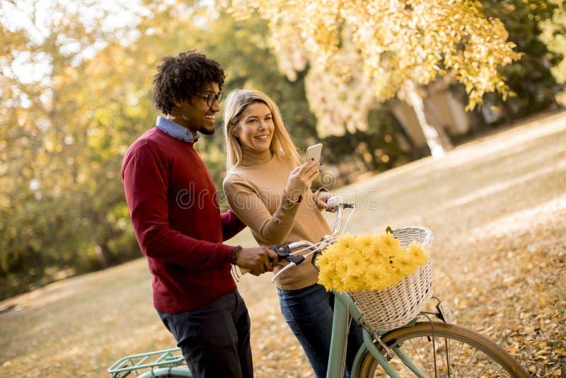 Pares multirraciais com a bicicleta no parque do outono fotografia de stock royalty free