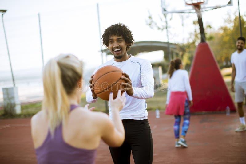 Pares multirraciais que jogam o basquetebol na corte exterior fotos de stock