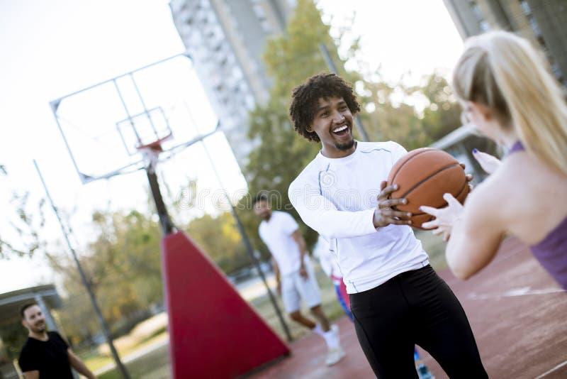 Pares multirraciais que jogam o basquetebol na corte exterior no dia do outumn fotos de stock royalty free