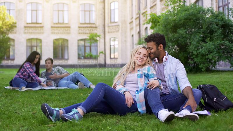 Pares multirraciais que relaxam na grama, abraçando e sorrindo, primeiro amor, estudantes fotos de stock royalty free
