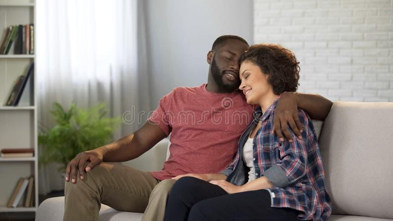 Pares multirraciales blandos que abrazan, teniendo resto en la comodidad casera, matrimonio feliz imagenes de archivo