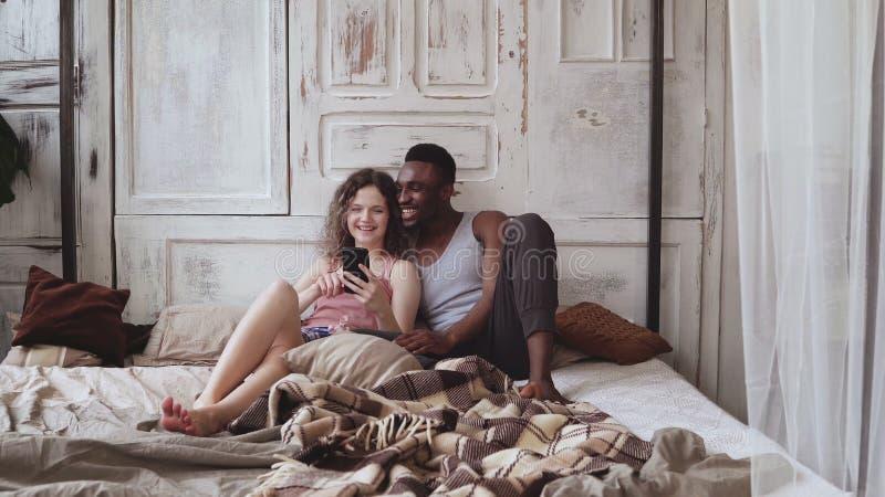 Pares multirraciales en los pijamas que se sientan en cama y smartphone del uso Hombre africano y mujer europea que miran las fot foto de archivo