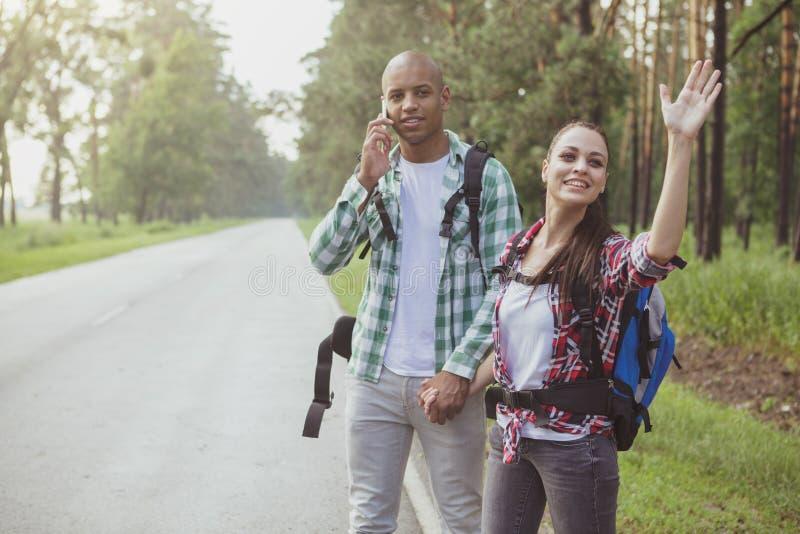 Pares multirraciales encantadores que hacen autostop junto foto de archivo libre de regalías