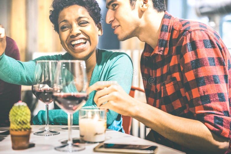 Pares multirraciales felices de los amantes que beben el vino tinto en el lagar de la barra de la moda imagen de archivo libre de regalías
