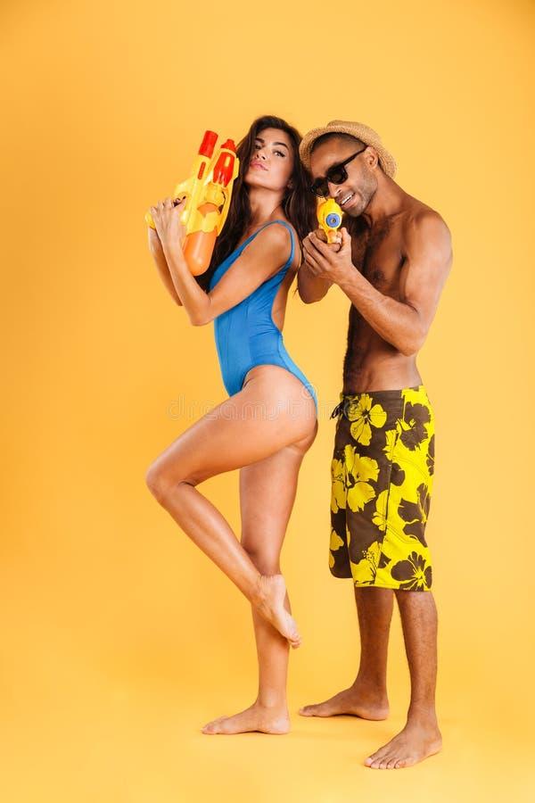 Pares multirraciales felices jovenes que se divierten que juega con los armas de agua imagenes de archivo