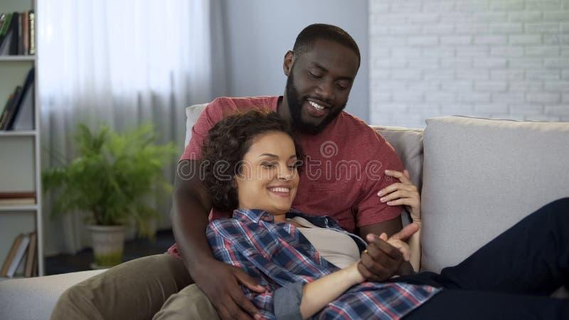 Pares multirraciales hermosos que tienen pasatiempo agradable junto en casa, matrimonio fotos de archivo libres de regalías