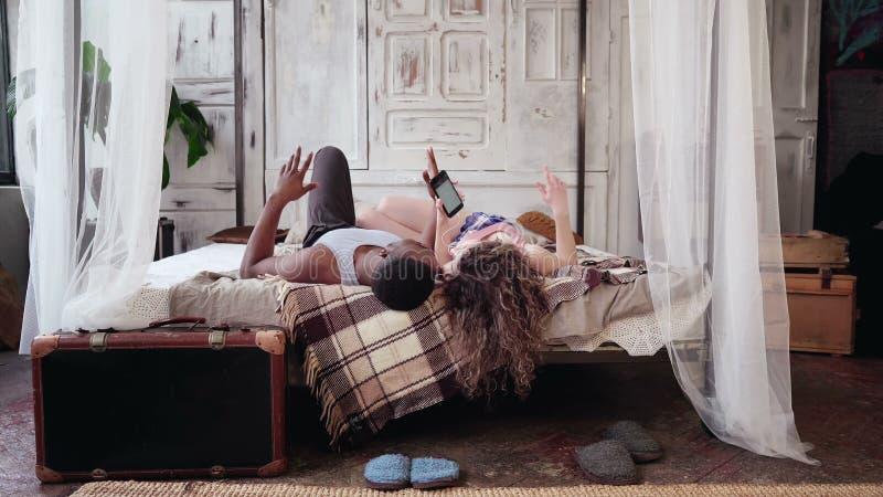 Pares multirraciales que mienten en cama, música que escucha en smartphone Hombre y mujer en pijamas que pasan mañana junto imágenes de archivo libres de regalías