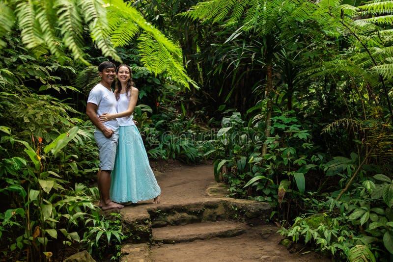 Pares multirraciales sonrientes felices que abrazan en rastro que camina en pares jovenes de la raza mixta del bosque tropical de imagenes de archivo
