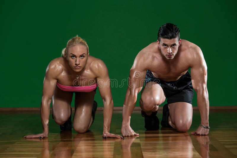 Pares musculares fortes que ajoelham-se no assoalho fotografia de stock