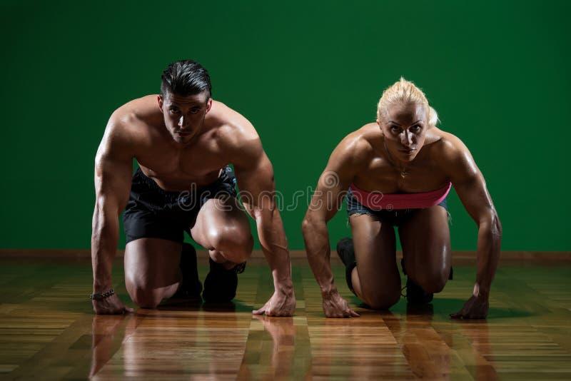 Pares musculares fortes que ajoelham-se no assoalho fotos de stock