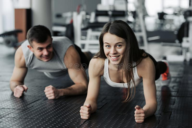 Pares musculares jovenes que hacen haciendo entrenamiento duro en el gimnasio Hacer el tablón en el gimnasio imágenes de archivo libres de regalías