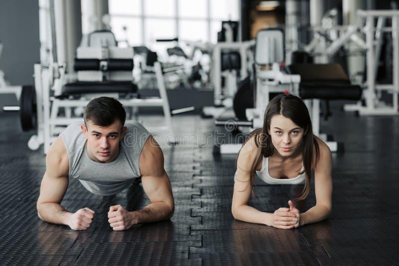 Pares musculares jovenes que hacen haciendo entrenamiento duro en el gimnasio Hacer el tabl?n en el gimnasio imagen de archivo libre de regalías